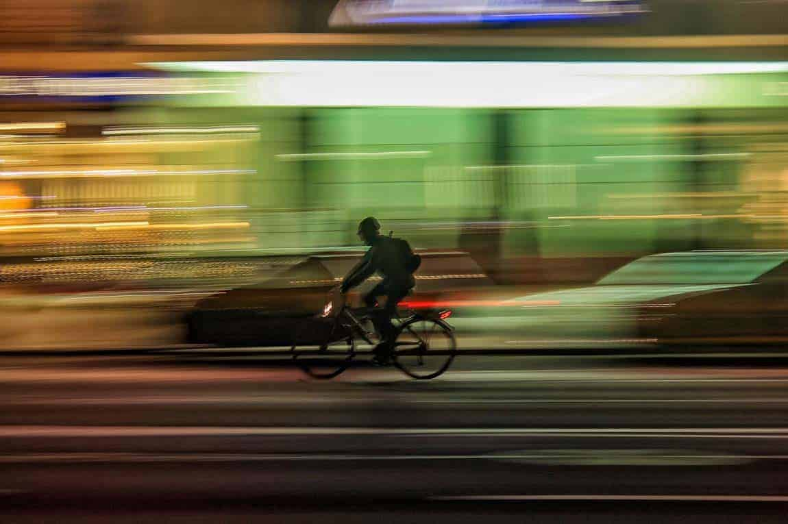 Man speeding past on a bicycle. Speed is a very important web hosting feature.
