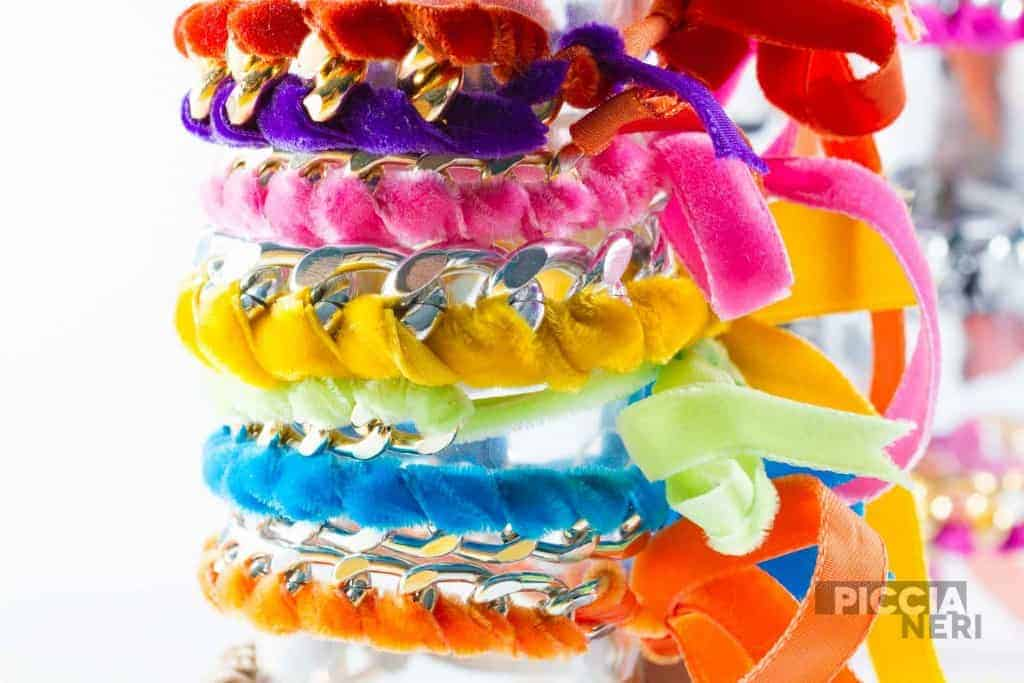 Fashion accessories: very colourful bracelets made by weaving velvet ribbons and metal chains together.