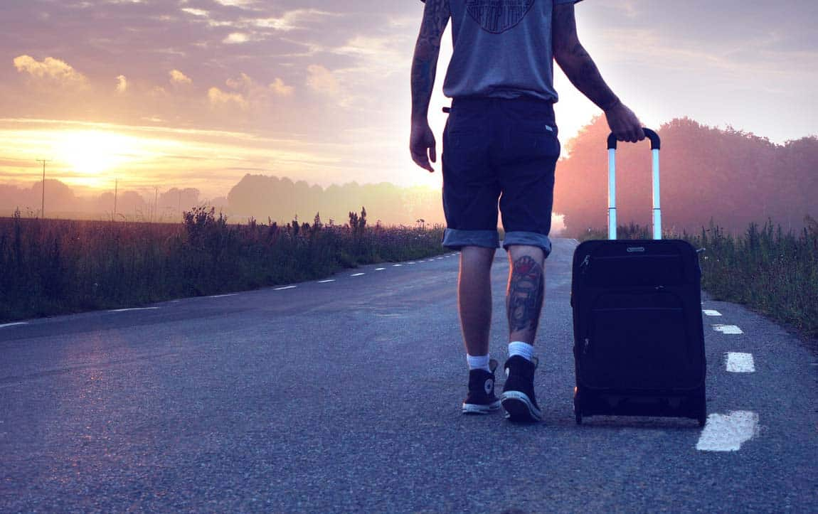 A man with a trolley suitcase walking towards the sunset in the middle of a deserted tarmac road. Take WordPress with you, everywhere.