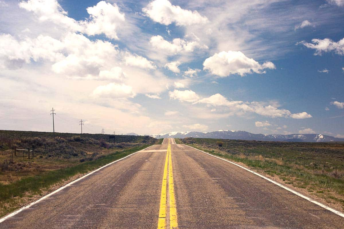 A straight asphalt road with double yellow line in the middle stretching all the way to the horizon, blue sky with clouds. WordPress is better than Wix or SquareSpace because it gives you freedom.