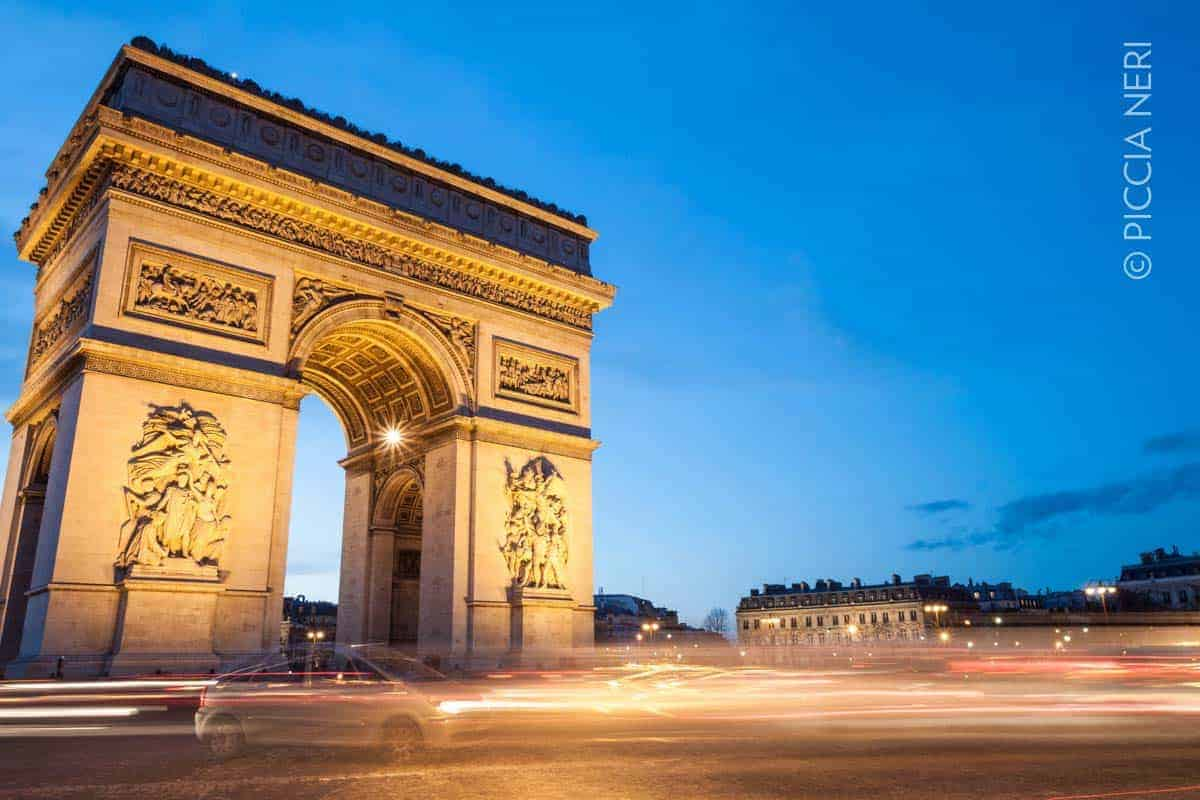 The Arc de Triomphe in Paris, France, at twilight with traffic light trails. Photo by Piccia Neri, all rights reserved.