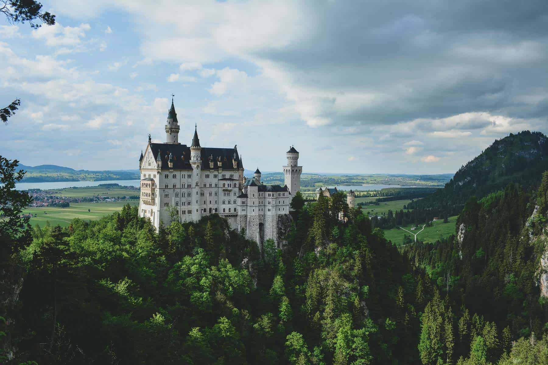 A gothic castle on top of a mountain, in the middle of a green mountain landscape.