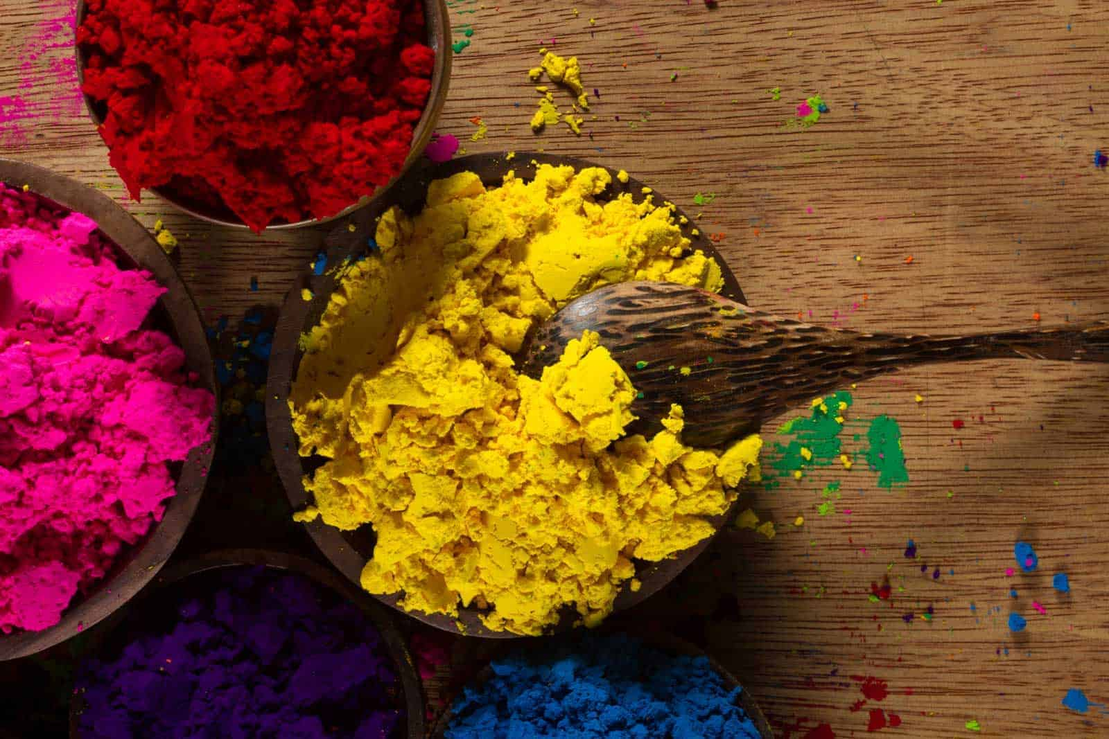 Colorful, finely powdered Indian pigments with a measuring spoon in the yellow.