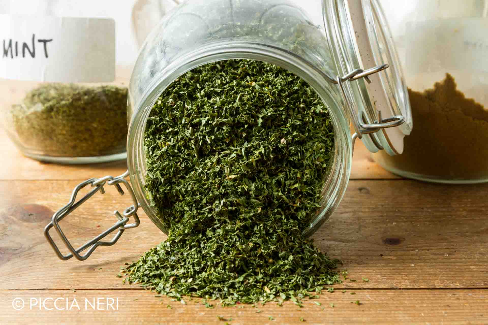 Middle Eastern cuisine: a jar of dried parsley with other herbs in the background.