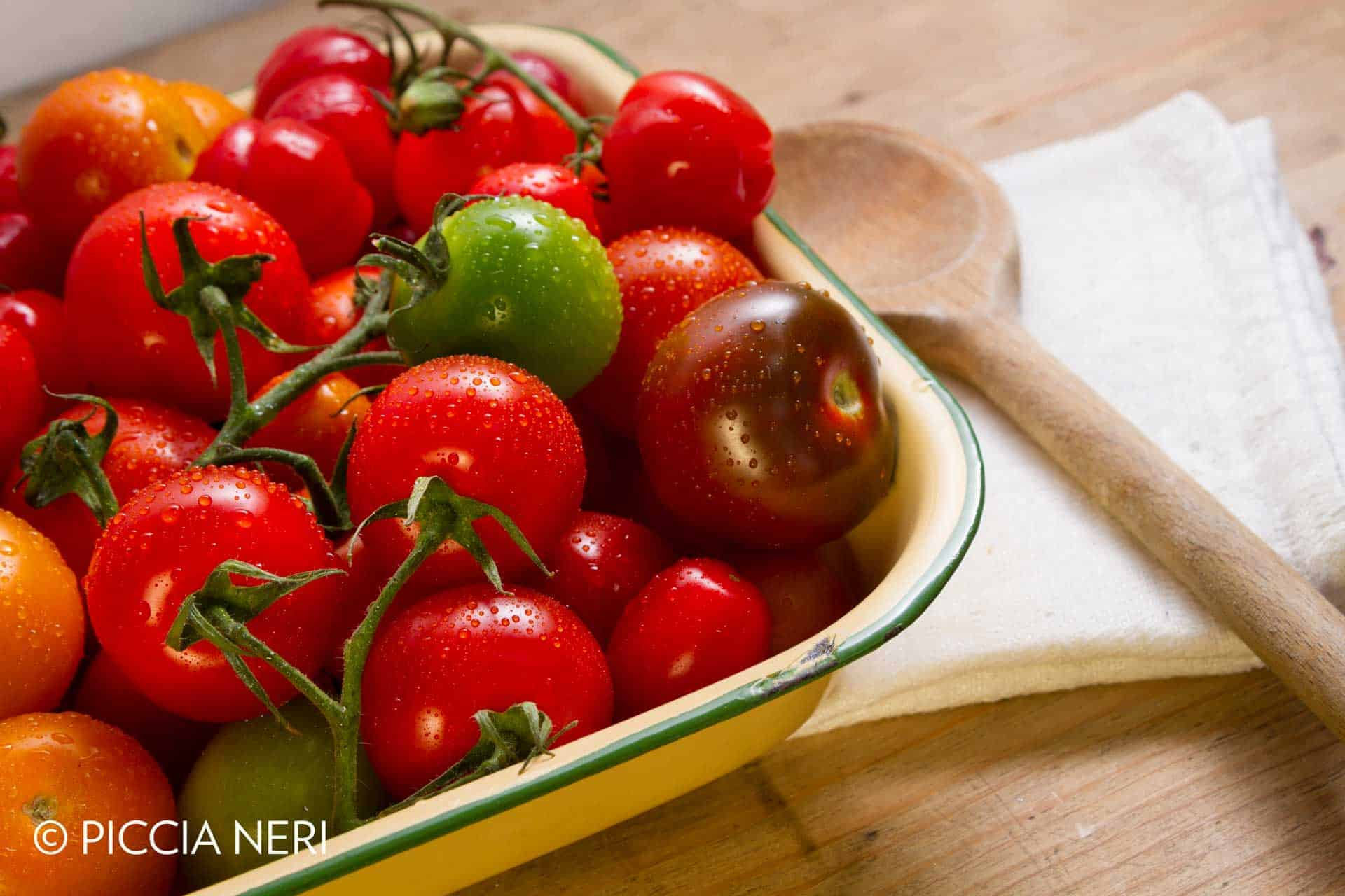 Ripe, organically grown tomatoes in a variety of colours: yellow, orange green brown and red.