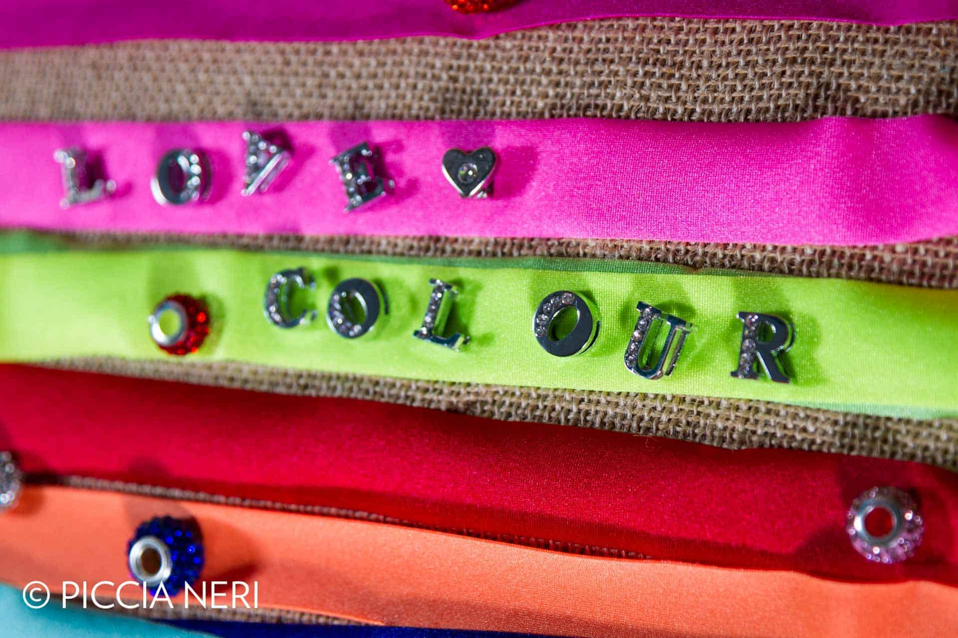 Lycra ribbons in bright, fluorescent colours with studded metal letters spelling 'Love Colour'. Photo by Piccia Neri, all rights reserved.